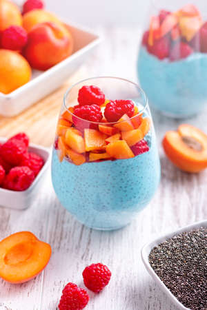 Chia seeds blue pudding with apricot, raspberry in glasses on white wooden background with fruits scattered around. Mousse with chia seeds, berries and fruits for healthy breakfast, top view