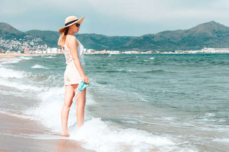 Woman in sunglasses and straw hat wearing medical mask at sea beach, new normal rules, web banner. Life after pandemic, obligatory use of face mask in public spaces, copy space