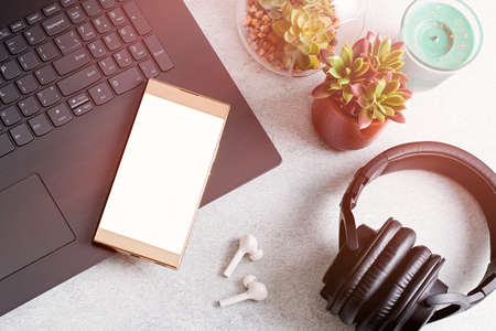 Blank screen smartphone on desk with laptop computer, wireless earphones, succulent plants on concrete table top, top view, copy space. Gadgets and home decor on grey table