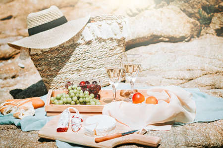 Romantic picnic for two on sea beach with white wine, fruits, bread and cheese. Mediterranean picnic with two glasses of wine, grapes, sweet cherry Stockfoto