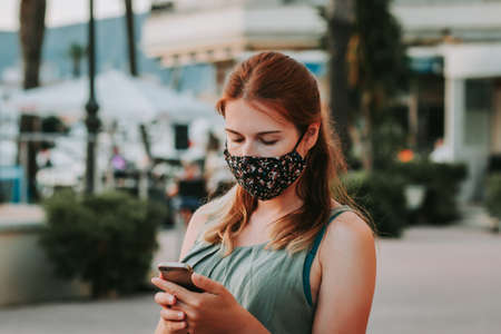 Woman in protective fashionable face mask with smartphone in a touristic place during covid new normal with crowded street cafe in background, sunset time