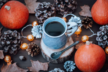 Mug with hot coffee and dry leaves, pumpkins, cones on wooden table, autumn lifestyle, top view Reklamní fotografie