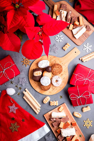 Traditional Spanish Christmas sweets turron, polvorones, mantecados with Christmas decor and red gift boxes on grey table top, copy space