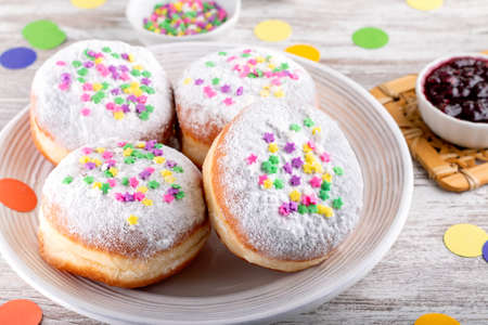 Carnival sprinkled doughnuts and confetti, holiday celebration, baking, top view 스톡 콘텐츠