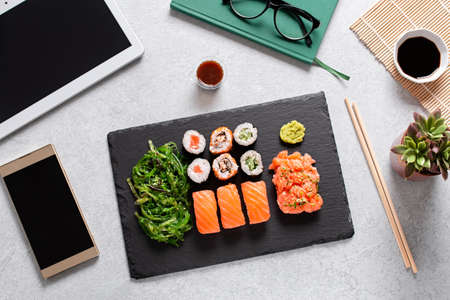Sushi takeaway at work desk with laptop overhead. Eating sushi for lunch break at office, lunch meal at work, top view