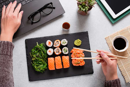 Woman eating sushi takeaway at work desk and working overhead. Eating sushi for lunch break, lunch meal at work, eating at work 스톡 콘텐츠