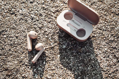 True wireless earbuds in case on natural stone background, top view,closeup, copy space 스톡 콘텐츠
