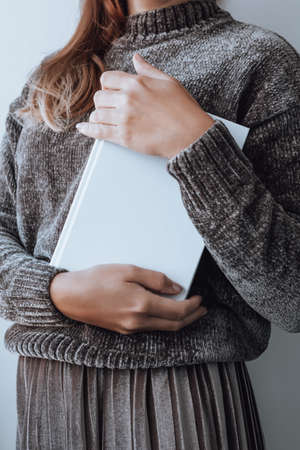 Faceless woman holding stack of white books, books closeup, education concept