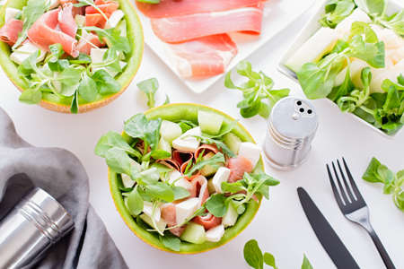 Summer mediterranean salad with ham and melon on white table top 스톡 콘텐츠