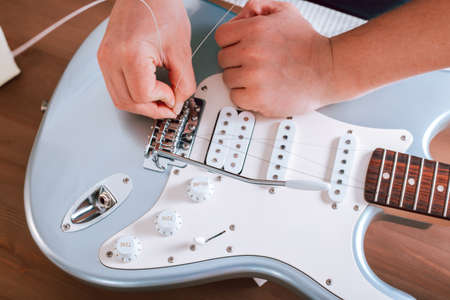 Guitar master restringing electric guitar, top view, closeup 스톡 콘텐츠
