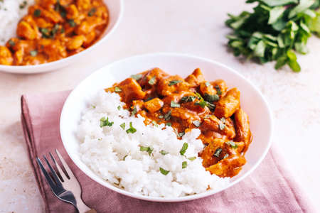 Chicken tikka masala and rice in white bowl on neutral table top