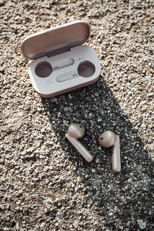 True wireless earbuds in case on natural stone background