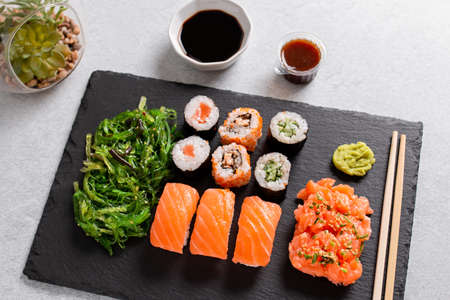 Sushi takeaway with chopsticks and sauces on concrete background, top view