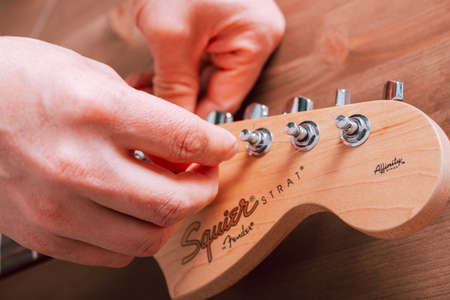 EMPURIABRAVA, SPAIN - FEBRUARY 17, 2021 Guitar master changing guitar strings on Fender Squier Strat
