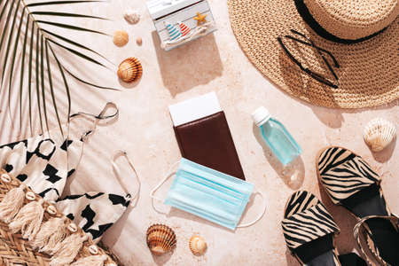 Travel flat lay with passport, clothes, beach accessories, mask and hands sanitizer