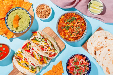 Mexican food table with traditional dishes. Chili con carne, tacos, tomato salsa, corn chips with guacamole 스톡 콘텐츠