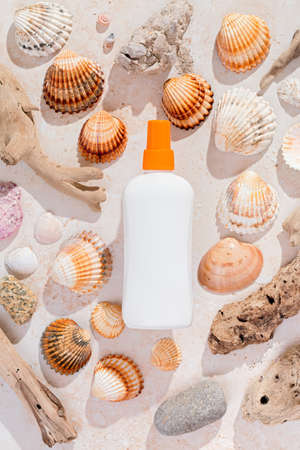 Bottle of sunscreen on background of seashells in hard light, top view. Sun protection lotion flat lay, creative image