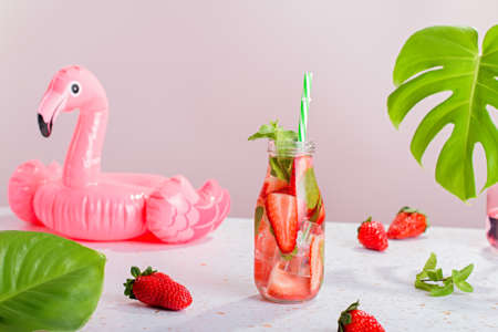 Strawberry and mint infused water in glass bottle on table, still life with summer cocktail, monstera leaf