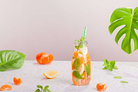 Orange and mint infused water in glass bottle on table, still life with summer cocktail, straw hat, monstera leaf