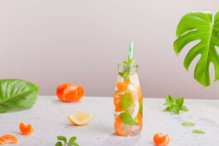 Orange and mint infused water in glass bottle on table, still life with summer cocktail, straw hat, monstera leaf. Summer refreshment