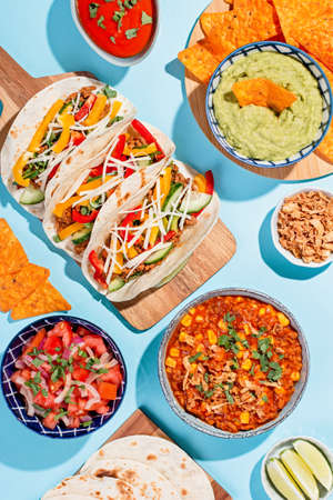 Mexican food table with traditional dishes. Chili con carne, tacos, tomato salsa, corn chips with guacamole. Mexican feast in hard light on blue color background, top view