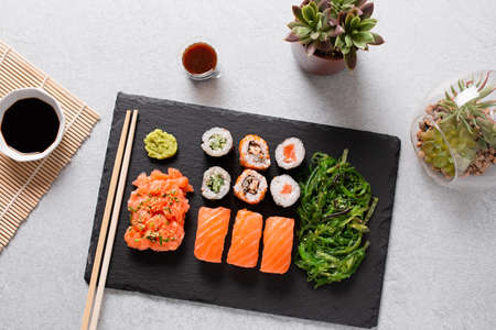Sushi takeaway with sushi set, wakame salad, chopsticks and sauces on gray concrete background, top view 스톡 콘텐츠