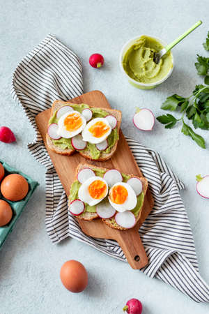 Healthy avocado and egg toasts for breakfast on board, top view, natural lighting