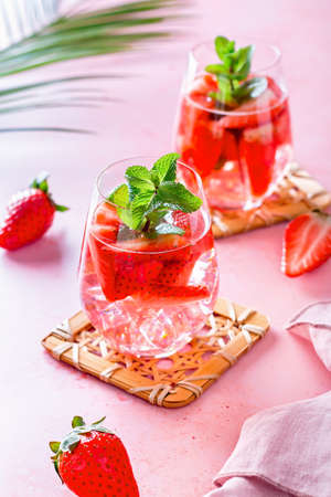 Summer mint and strawberry infused water on pink table top, still life, top view. Summer fruity refreshing cocktail still life closeup