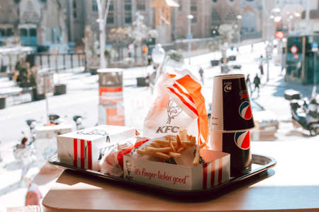 BARCELONA, SPAIN - MARCH 24, 2021: Kfc menu on table in cafe with Sagrada Familia Basilica in background 에디토리얼