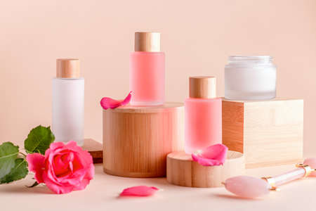 Facial serum and cream with rose extract on wooden podiums