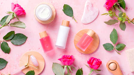 Rose extract natural cosmetics in reusable bottles with gua sha facial beauty roller and natural rose flowers on pink, top view Imagens
