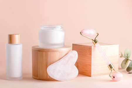 Facial serum and cream on wooden podiums, natural cosmetics concept
