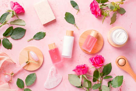 Rose extract natural cosmetics in reusable bottles with gua sha facial beauty roller and natural rose flowers on pink, top view