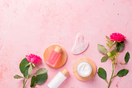 Rose extract natural cosmetics in reusable bottles with gua sha facial beauty roller and natural rose flowers on pink, border with copy space Imagens