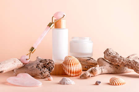 Scincare cosmetics, facial moisturizer, gua sha beauty roller on podiums with seashells