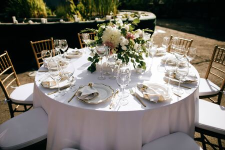 elegant table setting with floral decor in the garden, outdoor catering service
