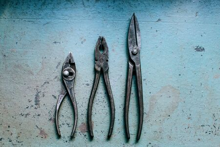 flat lay. Old Pliers on the blue metal table, working tools grunge background