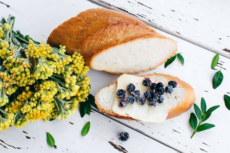 Delicious sandwich with blueberries and butter on a white background