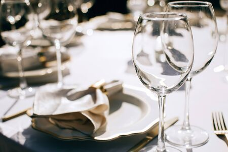 table set for dinner with wine glasses in the summer garden. Outdoor catering