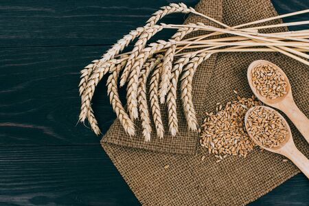 Ears of Wheat and spoon of Wheat Grains on wooden table Zdjęcie Seryjne