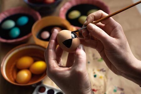 Woman paints chicken eggs with funny patterns. Easter decoration