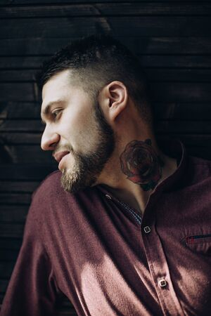 Portrait of a brutal bearded man with a tattoo on his neck