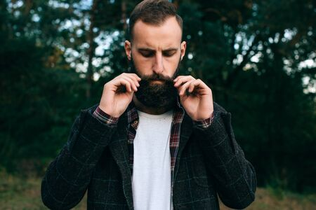 Young hipster man straightens his mustache in the forest Banque d'images