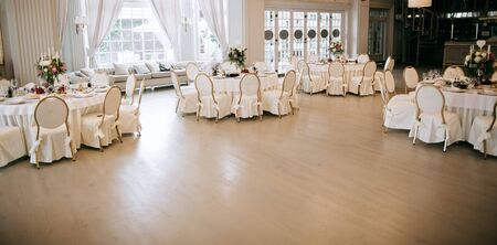 Elegant wedding reception white table arrangement, decoration with flowers and candles