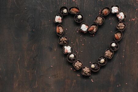 heart with chocolate candy on vintage wooden background. Love concept. rustic style