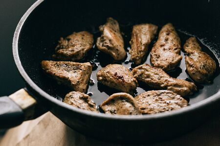 Cooking process. Fried chicken steak in a frying pan. fatty junk food Фото со стока
