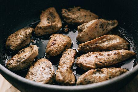Fried meat in a frying pan. fatty junk food Фото со стока