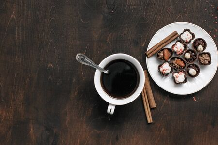 Cup of coffee with chocolate candies on wooden background