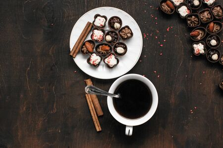 cup of coffee and chocolate candy on wooden table. Morning breakfast. Work, relax concept