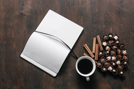 Top view. Cup of coffee with chocolate candies and a Notepad on wooden background. Work and relax space concept Фото со стока